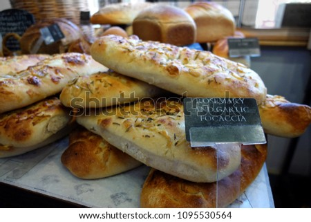 Shallow focus close up of rosemary and garlic focaccia bread, with other loaves in blurred background. #1095530564
