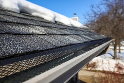 Shallow focus on mesh in gutter and shingles, gutter in winter and snow melted off of roof to prevent roof damage