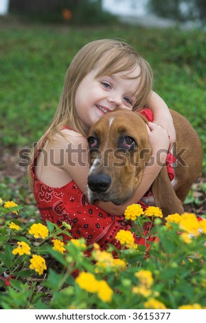 shallow focus portrait of little girl in flower bed with her dog