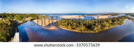Shallow Nambucca river flowing through sandy dunes and beaches of pacific ocean coast near Nambucca Heads where river enters the ocean in wide aerial panorama. #1070573639