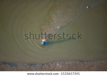 Shallow water fisherman fixing his net across a shallow water beach to trap fishes and prawns #1533657341