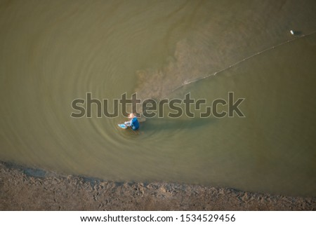 Shallow water fisherman fixing his net across a shallow water beach to trap fishes and prawns captured from different angles #1534529456