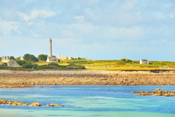 Shallow water of Lilia bay and the village near the Île Vierge lighthouse on a sunny day. Plouguerneau, Finistère, Brittany, France. Travel destinations, national landmark, recreation theme
