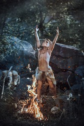 Shaman boy at the fire. Scary young primitive boy outdoors near bonfire. Witch craft concept. Angry caveman, manly boy with horns near bonfire. Prehistoric tribal man outdoors on nature making