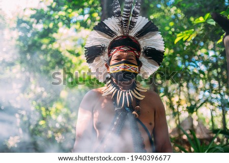 Shaman of the Pataxó tribe. Elderly Indian man wearing feather headdress and face mask due to the covid-19 pandemic. Brazilian Indian looking at the camera