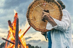 shaman plays drums near the big fire on the sky background