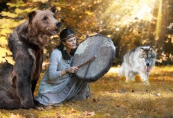 Shaman woman playing her shaman sacred drum in the forest among wild animals - a dog and a bear. Ethnic traditions