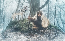 Shamanic man playing on shaman frame drum in the nature.