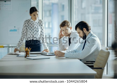 Shame on you. Strict young female boss frowning at her employees and scolding them in her office while they looking guilty and averting gaze