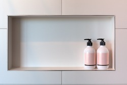 Shampoo and conditioner or shower gel dispensers in a rectangular niche made of white tiles with copy space