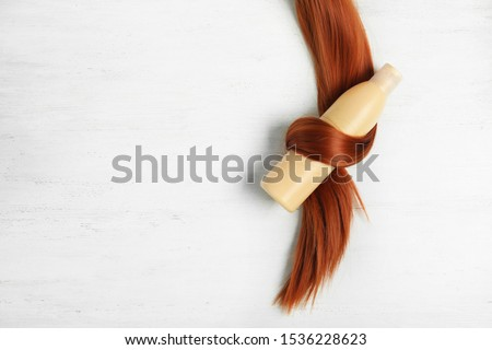 Shampoo bottle wrapped in lock of hair on white wooden background, flat lay with space for text. Natural cosmetic products