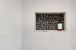 Shampoo / shower gel bottle in a rectangular niche made of black pebble mosaic tiles in shower and bathroom. Brown shampoo bottle with white sticker