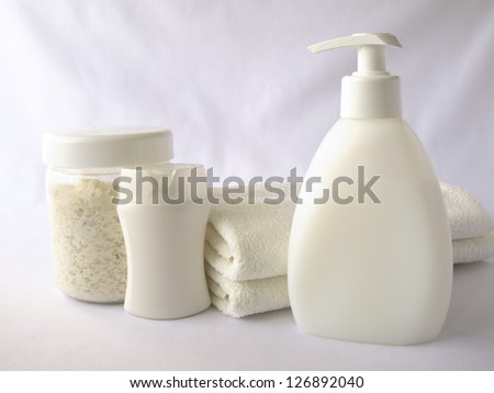 Shampoo, shower gel, towels on white background