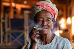 Shan State, Myanmar (Burma), old lady of Pa O ethnic minority smoking a Burmese cigar at Indein village near Inle Lake.