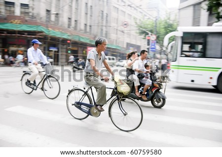 SHANGHAI - AUGUST 21: Unidentified men ride their bicycles in Shanghai on August 21, 2009.  Bicycles are a common form of transportation in China.