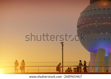 SHANGHAI, CHINA - March 29: Office people passing the Oriental Pearl Tower after getting off work on March 29, 2015 in Shanghai, China. More than 20K people working at this Shanghai finance  area.