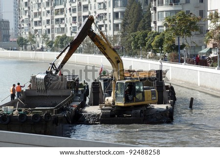 SHANGHAI, CHINA - NOVEMBER 27: An excavator digs to deepen the river bed in a flood mitigation project on November 27, 2011 in Shanghai, China. Shanghai had been badly hit by floods in the past.
