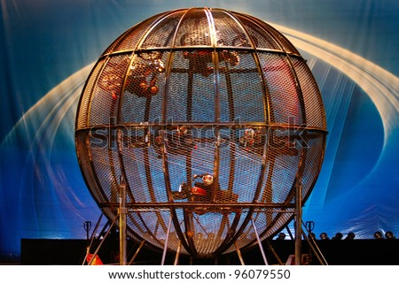 SHANGHAI, CHINA - NOVEMBER 28: Stuntmen from the famous Shanghai acrobats team ride motorbikes at high speed spinning inside a steel cage for tourist on stage on November 28, 2011 in Shanghai, China.