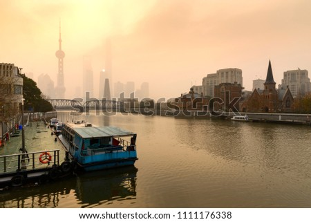 Shanghai Financial Center and modern skyscraper city in misty gold lighting sunrise behind pollution haze, view from the bund in Shanghai, China. vintage picture style