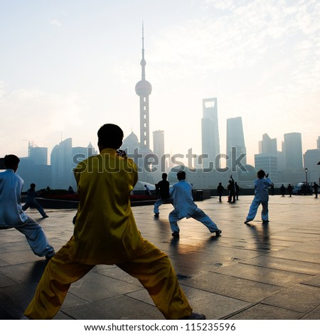 SHANGHAI - NOV. 21:  People practice Taiji on the Bund , Oriental Pearl Tower in the distance, on November 21, 2010 in Shanghai, China.  One of the top ten attractions in Shanghai.