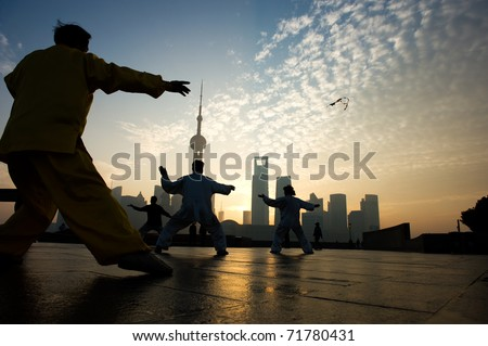 SHANGHAI - November 21:  People playing Taiji on the Bund , Oriental Pearl Tower in the distance, on November 21, 2010 in Shanghai, China.  One of the Top Ten Shanghai Attractions.