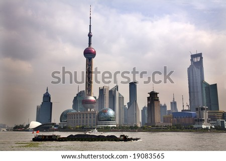 Shanghai Pudong China Skyline Daytime TV Tower with Coal Barge in front  Trademarks removed.