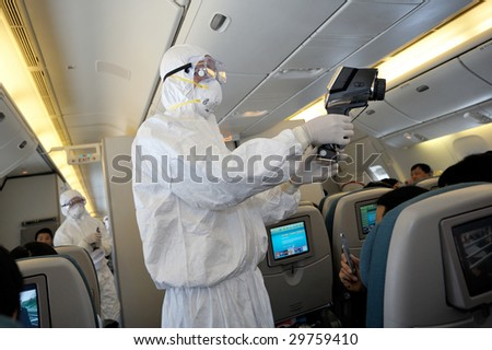 SHANGHAI, PUDONG DISCTRICT - MAY 5: Health officials from quarantine department make passengers body heat checkup on board of the flight from Auckland at the Shanghai airport May 5, 2009 in Shanghai.