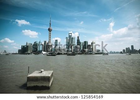shanghai skyline with huangpu river against a blue sky