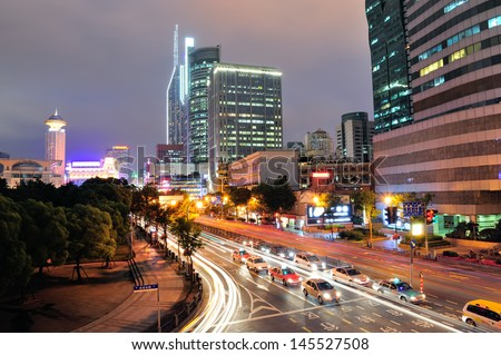 Shanghai street view with urban scene and busy traffic at dusk.