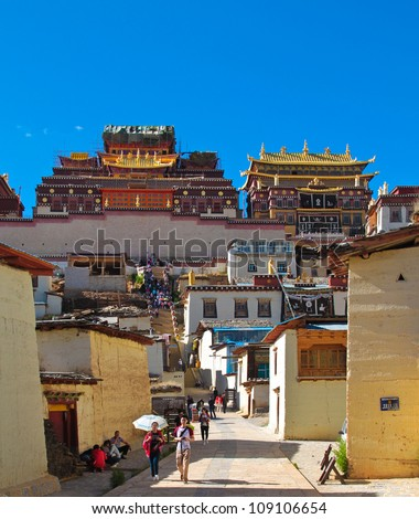 SHANGRI-LA, CHINA- CIRCA JUNE 2012: Anonymous tourists come to admire the view of Songzanlin Monastery, the largest Tibetan monastery during spring time at Shangri-la, Yunnan China circa June 2012.