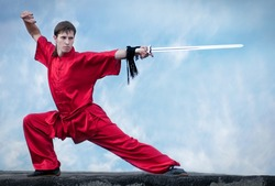 Shaolin warriors wu shoo man in red with sword practice martial art outdoor. Kung fu