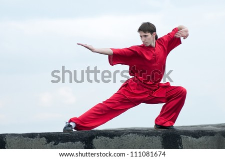 Shaolin warriors wushoo man in red practice martial art outdoor. Kung fu