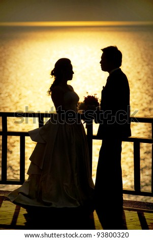 Shape of a bride and groom on the beach at sunset time