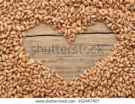 shape of the heart is made of wheat against a wooden background