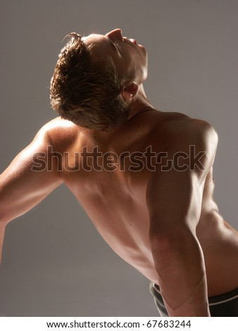 Shaped and young man stretching his muscles. - stock photo