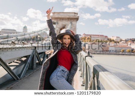 Shapely blissful girl in red sweater dancing on bridge on blur city background in autumn morning. Outdoor photo of happy female tourist having fun, exploring attractions.