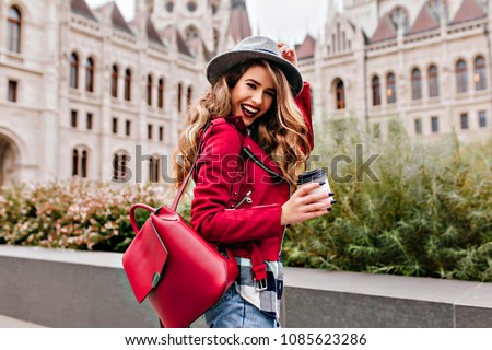 Shapely girl with wavy hair laughing while exploring old part of city. Charming female tourist in hat holding cup of coffee and smiling. #1085623286