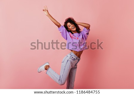 Shapely jocund girl dancing on rosy background. Good-humoured african lady jumping with smile.