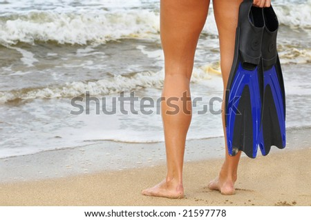 Shapely legs of a young woman on beach with flippers, ready for the water