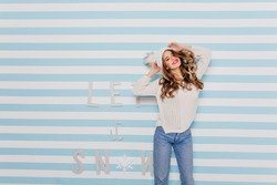 Shapely woman in vintage jeans dancing on blue striped background. Studio shot of caucasian brunette girl in white sweater expressing positive emotions.