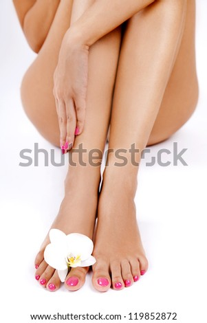 Shapely woman's legs with an orchid flower between toes
