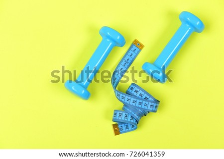 Shaping and fitness equipment. Sports and healthy lifestyle concept. Dumbbells and measure tape in cyan blue color on light yellow background, top view. Barbells next to roll of tape measure #726041359