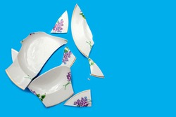 Shards of a broken plate on a blue background. Small pieces of chopped dishes