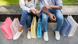 Share with followers emotions and photo of shopping. African american couple making photo of purchases in bags, sitting on bench in park, panorama, cropped