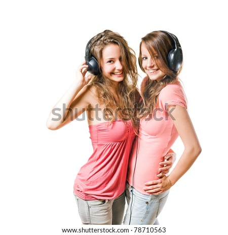 Share your tune, two gorgeous brunette teens having fun with headphones, isolated on white.
