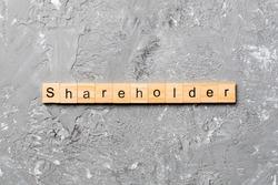 shareholder word written on wood block. shareholder text on table, concept.
