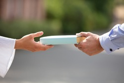 Sharing Books. Hand Closeup Giving Book Outdoors