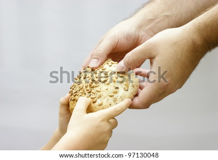 Sharing bread. Man giving bread to a small child. Charity concept.
