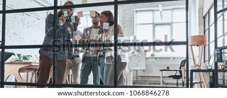 Sharing business ideas. Full length of young modern people in smart casual wear using adhesive notes while standing behind the glass wall in the board room #1068846278
