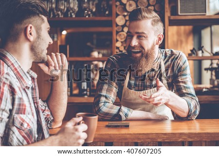Sharing good news. Barista and his customer discussing something with smile while sitting at bar counter at cafe #407607205